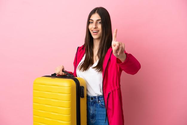 Joven mujer caucásica aislada sobre fondo rosa en vacaciones con maleta de viaje y contando uno