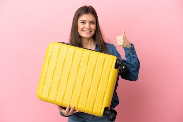 Joven mujer caucásica aislada sobre fondo rosa en vacaciones con maleta de viaje y con el pulgar hacia arriba