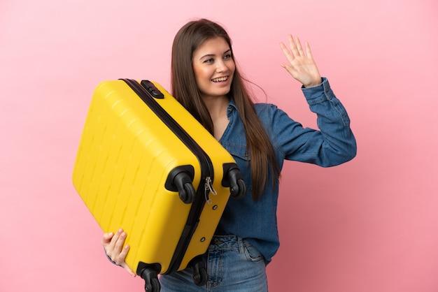Joven mujer caucásica aislada sobre fondo rosa en vacaciones con maleta de viaje y saludando