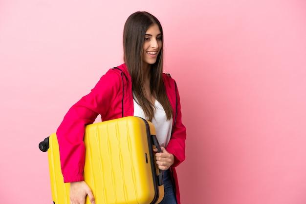 Joven mujer caucásica aislada sobre fondo rosa en vacaciones con maleta de viaje