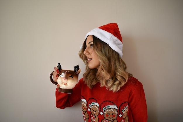 Joven mujer caucásica alegre en un lindo traje rojo de navidad y gorro de papá noel bebiendo chocolate caliente