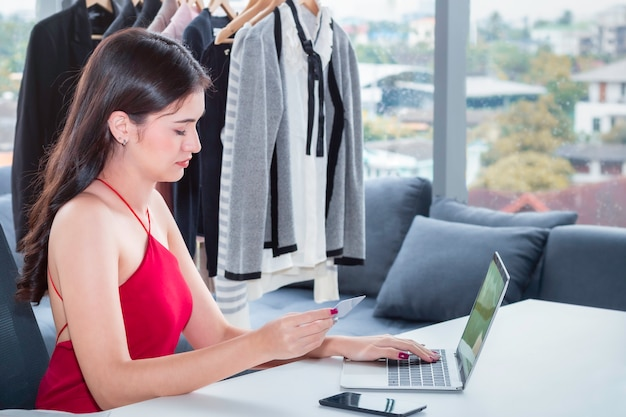 Joven mujer caucásica amigable trabajando con la computadora portátil y vendiendo compras de comercio electrónico en línea