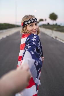 Joven mujer caucásica con la bandera de los estados unidos sobre sus hombros