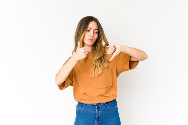 Joven mujer caucásica en blanco mostrando los pulgares hacia arriba y hacia abajo, difícil elegir el concepto
