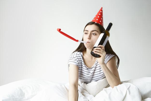 Joven mujer caucásica borracha en pijama de rayas se despertó temprano en la mañana después de la fiesta, sufriendo de resaca