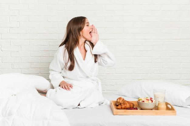 Joven mujer caucásica en la cama gritando y sosteniendo la palma cerca de la boca abierta.