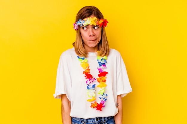 Joven mujer caucásica celebrando una fiesta hawaiana confundida, se siente dudosa e insegura.