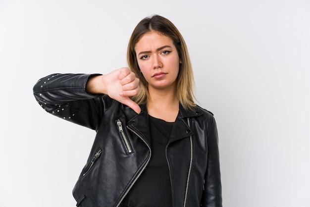 Joven mujer caucásica con una chaqueta de cuero negro que muestra un gesto de disgusto, pulgares hacia abajo. concepto de desacuerdo