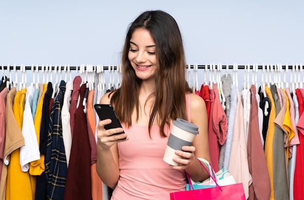 Joven mujer caucásica comprar algo de ropa en una tienda con café para llevar y un móvil