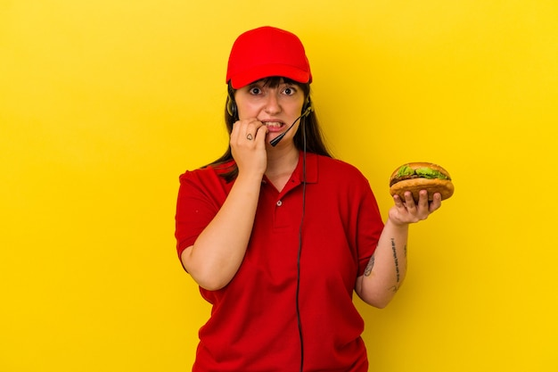 Joven mujer caucásica con curvas sosteniendo hamburguesa aislado sobre fondo amarillo mordiéndose las uñas, nervioso y muy ansioso.