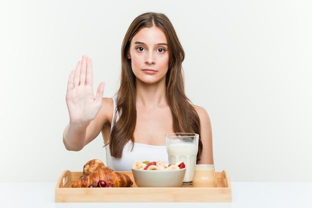 Joven mujer caucásica desayunando de pie con la mano extendida que muestra la señal de stop