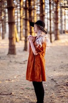Joven mujer caucásica en un elegante sombrero negro rezando en el bosque escénico, humor otoñal