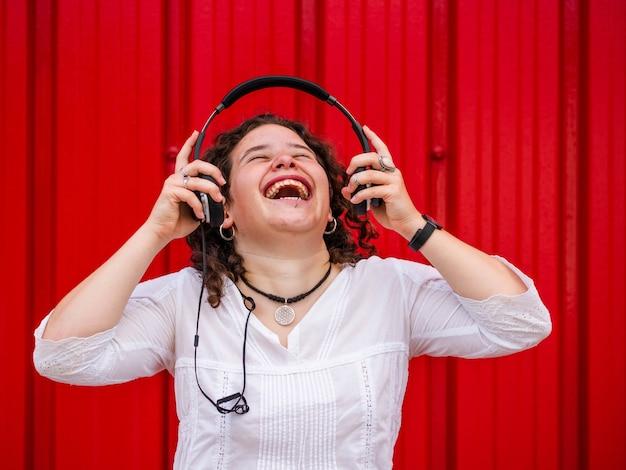 Joven mujer caucásica escuchando felizmente meditando con auriculares cerca de una pared roja
