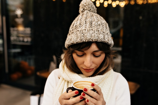 Joven mujer caucásica en gorro de punto tomando café y caminando por las calles con luces de humor navideño