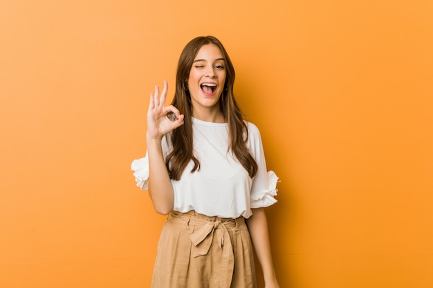 Joven mujer caucásica guiña un ojo y tiene un gesto bien con la mano.