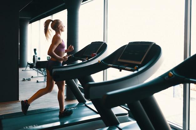 Joven mujer caucásica haciendo ejercicio con pesas mientras entrena brazos en el gimnasio