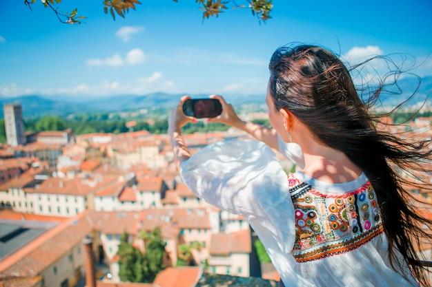 Joven mujer caucásica haciendo fotos de la ciudad vieja europea por teléfono móvil desde el lugar de observación