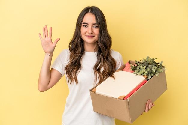Joven mujer caucásica haciendo un movimiento aislado sobre fondo amarillo sonriendo alegre mostrando el número cinco con los dedos.