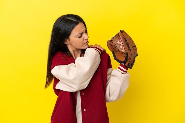 Joven mujer caucásica jugando béisbol aislado sobre fondo amarillo que sufre de dolor en el hombro por haber hecho un esfuerzo