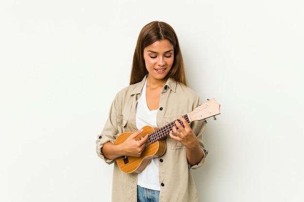 Joven mujer caucásica jugando ukelele