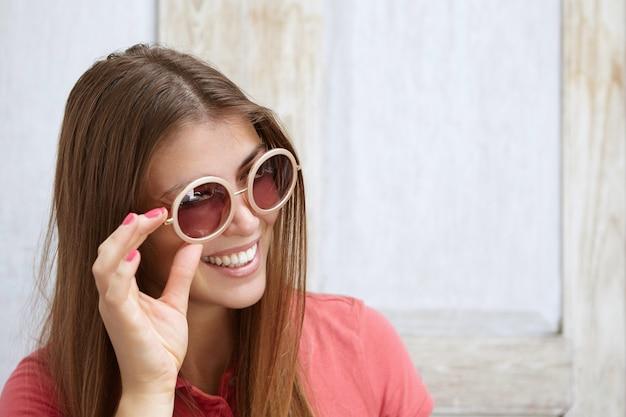Joven mujer caucásica con largo cabello rubio y uñas rosadas sonriendo mientras ajusta sus elegantes tonos redondos. mujer alegre divirtiéndose en el interior probándose gafas de sol.
