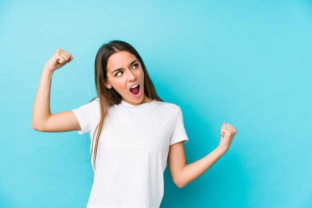 Joven mujer caucásica levantando el puño después de una victoria
