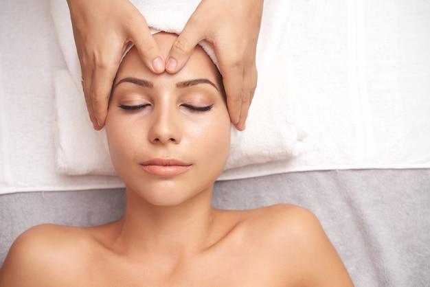 Joven mujer caucásica con masaje facial anti edad