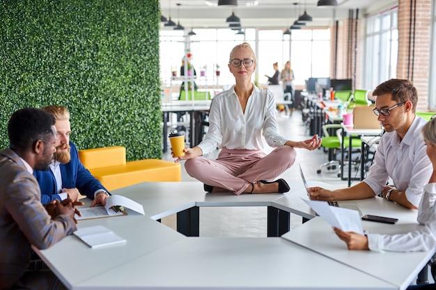 Joven mujer caucásica meditando en la oficina mientras sus colegas están trabajando