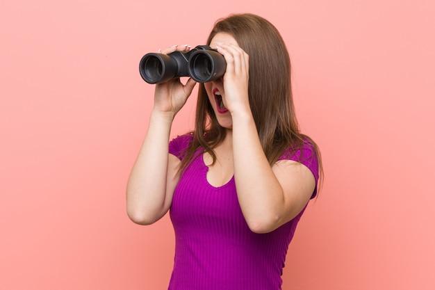 Joven mujer caucásica mirando a través de binoculares