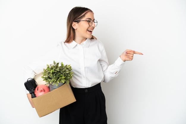 Joven mujer caucásica mudarse a casa nueva entre cajas aisladas en blanco dedo acusador hacia el lado y presentando un producto