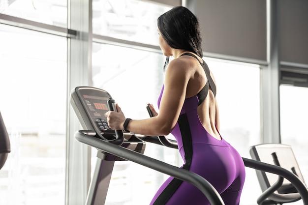 Joven mujer caucásica muscular practicando en el gimnasio con equipo
