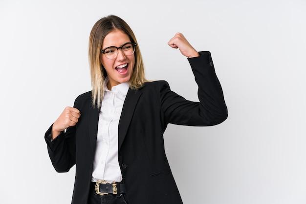 Joven mujer caucásica de negocios levantando el puño después de una victoria