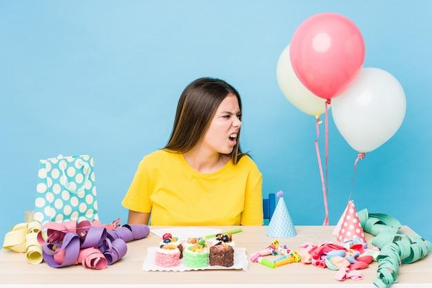 Joven mujer caucásica organizando un cumpleaños gritando hacia un espacio de copia