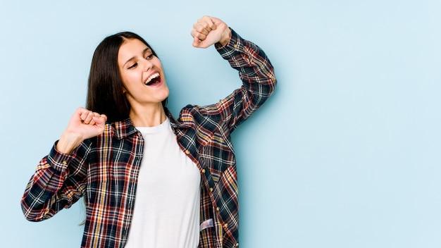 Joven mujer caucásica en pared azul celebrando un día especial, salta y levanta los brazos con energía.