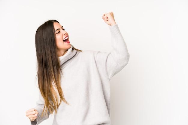 Joven mujer caucásica en una pared blanca levantando el puño después de una victoria