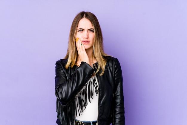 Joven mujer caucásica en pared púrpura con un fuerte dolor de dientes