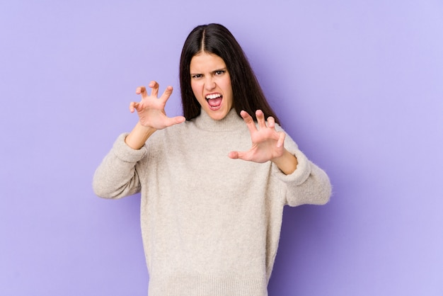 Joven mujer caucásica en pared púrpura mostrando garras imitando a un gato