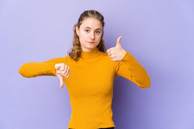 Joven mujer caucásica en pared púrpura mostrando pulgares arriba y pulgares abajo