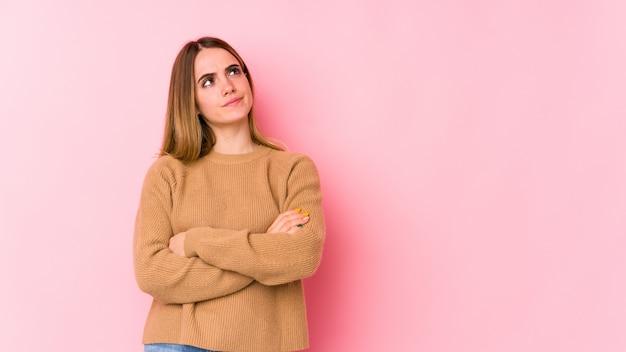 Joven mujer caucásica en pared rosa soñando con alcanzar objetivos y propósitos