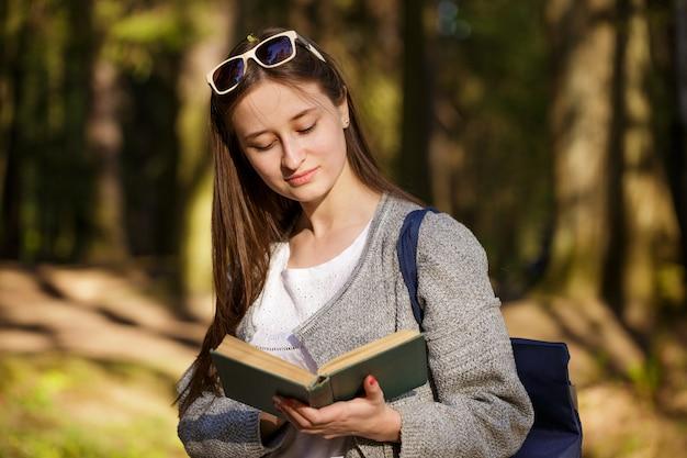 Joven mujer caucásica en el parque leyendo un libro en un día soleado de primavera