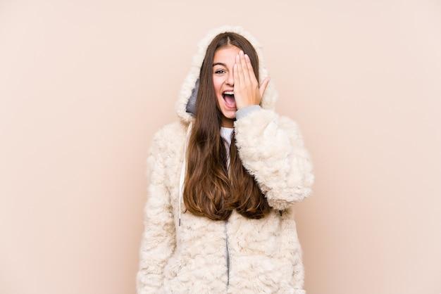 Joven mujer caucásica posando aislada divirtiéndose cubriendo la mitad de la cara con la palma.