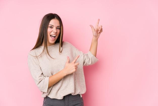 Joven mujer caucásica posando aislado apuntando con los dedos índice a un espacio de copia, expresando emoción y deseo