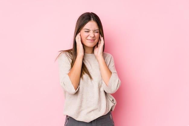 Joven mujer caucásica posando aislado cubriendo los oídos con las manos.