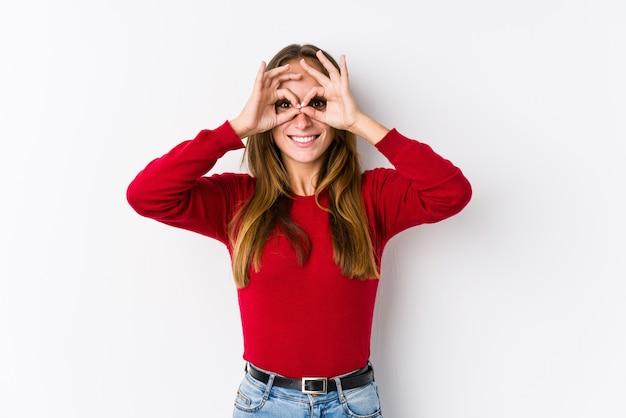 Joven mujer caucásica posando aislado mostrando bien firmar sobre los ojos