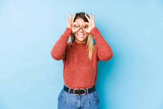 Joven mujer caucásica posando mostrando signo bien sobre los ojos