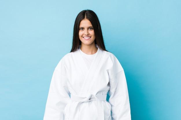 Joven mujer caucásica practicando karate aislado en una pared azul
