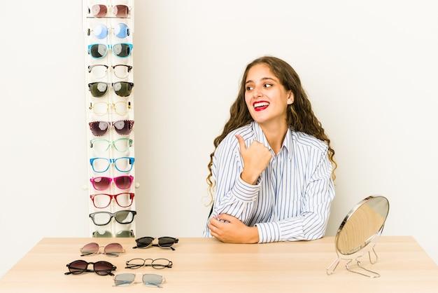 Joven mujer caucásica probando gafas aisladas