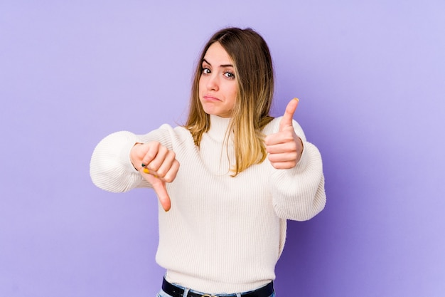 Joven mujer caucásica en púrpura mostrando los pulgares hacia arriba y hacia abajo, difícil elegir el concepto