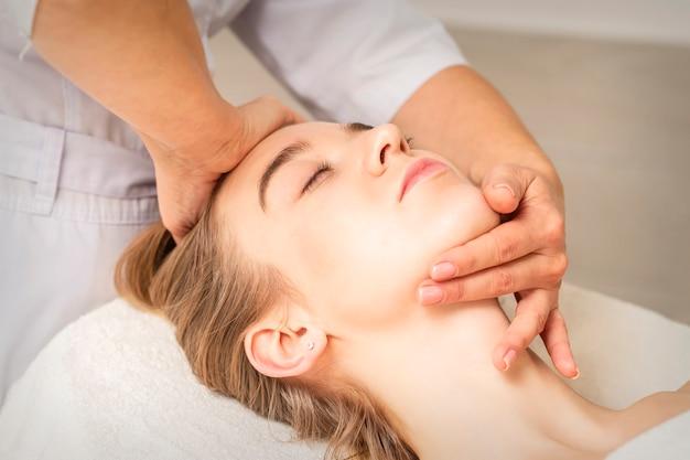 Joven mujer caucásica recibiendo un masaje de cabeza y barbilla en un centro médico spa