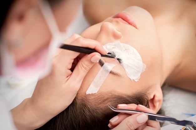 Joven mujer caucásica recibiendo procedimiento de extensiones de pestañas en salón de belleza
